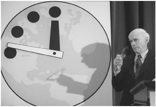 """รูปที่ 1 """"นาฬิกาสิ้นโลก"""" ที่ใช้เป็นหน้าปกของวารสารอะตอมมิกไซแอนทิสต์มาตั้งแต่ปี 1947 แล้ว  เป็นสัญลักษณ์บอกถึงปัญหานานาประเภทที่มนุษย์ก่อขึ้นมาแล้วทำให้โลกเข้าใกล้กาลอวสานมากเพียงใดแล้วโดยดูจากเข็มยาวว่าใกล้เที่ยงคืนมากเท่าใด"""