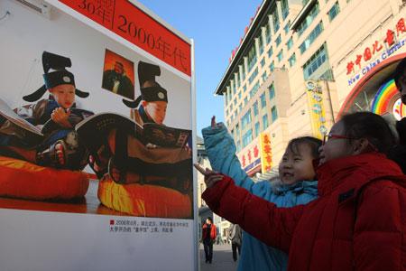 เด็กหญิงสองคนนี้กำลังชี้ชวนกันดูโปสเตอร์นิทรรศการรำลึก30 ปี ที่ถนนหวังฟู่จิ่งเมื่อวันที่ 17 ธันวาคม - ซีน่าเน็ต