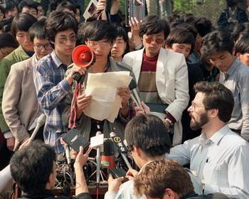 ภาพถ่ายเมื่อวันที่ 1 พฤษภาคม 2532 หวัง ตัน (กลาง) ผู้นำนักศึกษาที่มีความเห็นไม่สอดคล้องกับรัฐบาล และตัวแทนจากมหาวิทยาลัยปักกิ่ง กำลังแถลงการณ์แก่กลุ่มผู้สื่อข่าวในกรุงปักกิ่ง