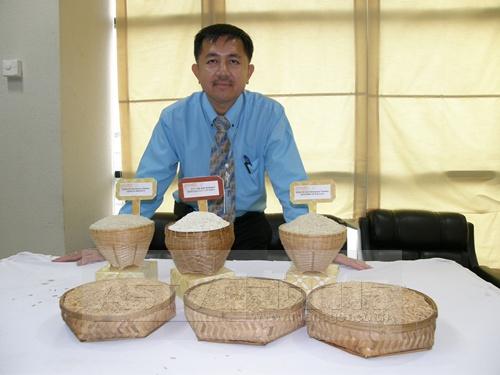 ดร.ธีรยุทธ ตู้จินดา กับข้าว 3 สายพันธุ์ใหม่ ที่ได้จากความร่วมมือวิจัยระหว่าง สวทช. และกรมการข้าว เมื่อปี 2549-2552