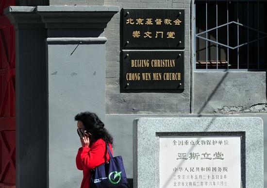 สตรีคนหนึ่งเดินผ่านโบสถ์คริสต์ฯ ในกรุงปักกิ่ง 17 เม.ย. หลังจากจีนจับกุมศาสนิกชนที่ประกอบพิธีกรรมนอกโบสถ์ 2 ครั้ง ทำให้โบสถ์ในปักกิ่งเงียบเหงาลงไปมาก ทั้งนี้เมื่อวันที่ 19 เม.ย. โบสถ์ได้เรียกร้องให้ศาสนิกชนมาประกอบพิธีวันอีสเตอร์อีก (ภาพเอเอฟพี)