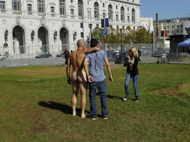A dressed man poses for a picture with a nude man at Civic Center Plaza in San Francisco, California October 30, 2012. Nudists converged on City Hall to protest city Supervisor Scott Wieners proposal to restrict public nudity in the city. REUTERS/Robert Galbraith