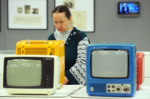 Moscow, RUSSIAN FEDERATION: A visitor looks at Soviet-era portable transistor TV sets displayed at the exhibition Soviet Design, 1950-1980, in Moscow, on December 5, 2012. Toys, kitchen utensils, furniture, posters, clothes, cars ... more than 200 objects and creations of all kinds objects designed for everyday life in the Soviet Union in 1950-1980 have been patiently gathered, from Russian museums, ancient designers, private collectors or recovered from private individuals through the Internet. AFP PHOTO/Andrey Smirnov