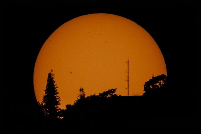 ภาพถ่ายดวงอาทิตย์เปรียบเทียบขนาดกับต้นไม้และเสาส่งสัญญาณวิทยุ บริเวณยอดดอยสุเทพ ในวันที่ 5 มกราคม 2556 โดยถ่ายภาพผ่านโซลาร์ฟิวเตอร์ ทางทิศตะวันตก ช่วงต้นปี 2556 ซึ่งเป็นช่วงครบรอบ 11 ปี ที่ดวงอาทิตย์เริ่มเข้าสู่ช่วงที่เรียกว่า Solar Maximum ทำให้มีจุดบนดวงอาทิตย์ค่อนข้างมากอย่างเห็นได้ชัด (ภาพโดย : ศุภฤกษ์ คฤหานนท์ : Canon EOS 7D / PVC Telescope 700 มม. / F10 / ISO 320 / 1/250 วินาที)