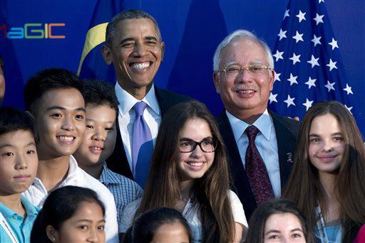"""ประธานาธิบดีบารัค โอบามา (ด้านหลังตรงกลางคนซ้าย) และนายกรัฐมนตรีนาจิบ ราซัค ของมาเลเซีย (ด้านหลังตรงกลางคนขวา) ถ่ายภาพพร้อมกับนักศึกษาหนุ่มสาว ขณะพวกเขาเดินทางไปเยี่ยมศูนย์นวัตกรรมและการสร้างสรรค์ระดับโลกของมาเลเซีย ที่เขตไซเบอร์จายา ของมาเลเซีย เมื่อวันอาทิตย์ (27) โอบามากำลังอยู่ระหว่างตระเวนเยือน 4 ชาติในเอเชีย เพื่อตอกย้ำยุทธศาสตร์ """"ปักหมุด"""" ในภูมิภาคนี้ของเขา"""