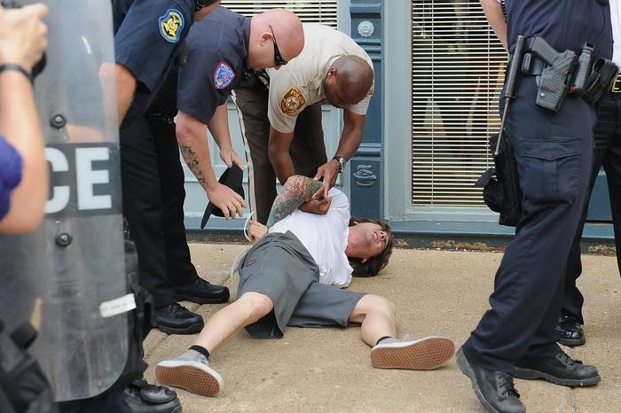 เจ้าหน้าที่ตำรวจควบคุมตัวผู้ชุมนุมคนหนึ่ง ที่ยืนประท้วงหน้ากองบัญชาการตำรวจเมืองเฟอร์กูสัน เมื่อวันจันทร์ (11 ส.ค.)