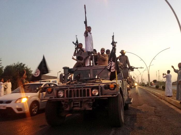 (แฟ้มภาพ) สมาชิกนักรบ รัฐอิสลาม (ไอเอส) นำยานพาหนะหุ้มเกราะที่ยึดมาจากกองกำลังอิรักออกลาดตระเวนในเมืองโมซุล ของอิรัก (23 มิ.ย.)