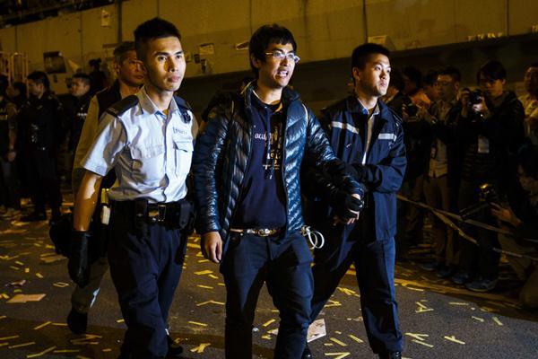 ผู้นำสหพันธ์นักศึกษา อเล็กซ์ โจว ถูกตำรวจจับกุมตัวออกไป (ภาพ รอยเตอร์ส)
