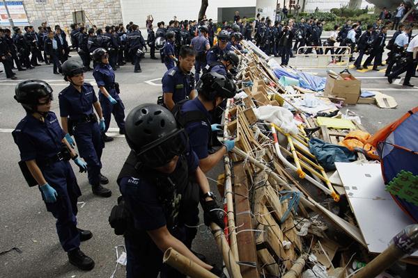 ตำรวจรื้อแนวกั้นที่กลุ่มประท้วงนำมาปิดถนนฯนอกสำนักงานรัฐบาล (ภาพ รอยเตอร์ส)