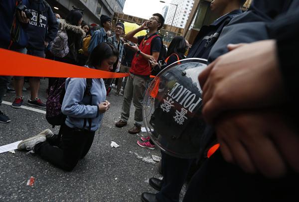 นักศึกษาคุกเข่าหลังจากที่ตำรวจขวางไม่ให้เข้ามาในพื้นที่ที่ที่กำลังเคลียร์ (ภาพ รอยเตอร์ส)