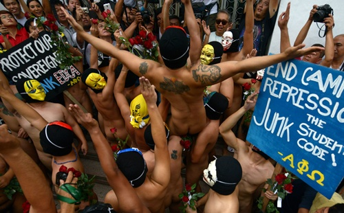 Manila, PHILIPPINES: A group of masked fraternity members in the state-run University of the Philippines hoist up a comrade (C) as they prepare to run naked through the campus during the annual Oblation Run, handing out roses to female students as part of their tradition, in Manila on December 12, 2014. This years run is dedicated to abolishing politician discretionary funds. AFP PHOTO/Jay Directo