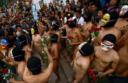 Manila, PHILIPPINES: A group of masked fraternity members in the state-run University of the Philippines run naked through campus during the annual Oblation Run, handing out roses to female students as part of their tradition, in Manila on December 12, 2014. This years run is dedicated to abolishing politician discretionary funds. AFP PHOTO/Jay Directo