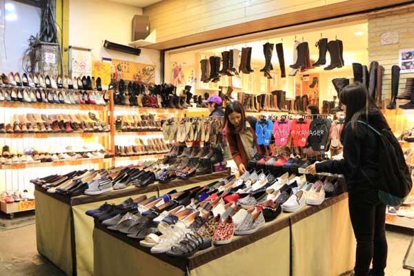 นักท่องเที่ยวเลือกซื้อรองเท้าที่ตลาดฝงเจี่ยไนท์มาร์เก็ต