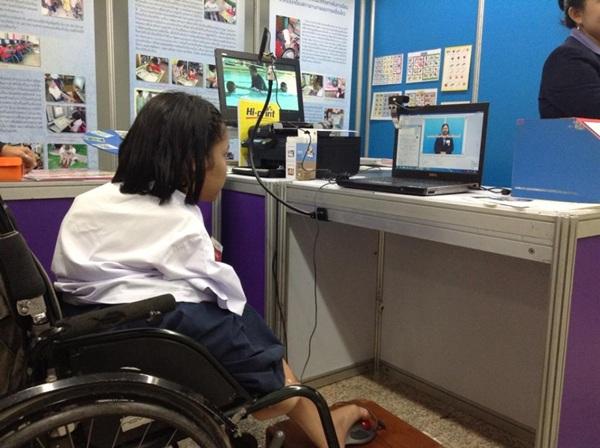 เยาวชนผู้พิการใช้เมาส์ที่ออกแบบมาพิเศษสำหรับควบคุมด้วยเท้าเมื่อแต่งภาพด้วยโปรแกรมคอมพิวเตอร์