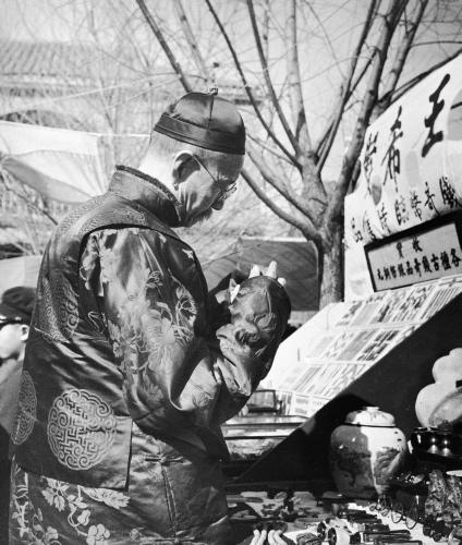 ลูกค้ากำลังยืนดูสินค้า ที่จำหน่ายในตลาดปีใหม่ ช่วงเทศกาลปีใหม่จีน โดยตลาดปีใหม่จีนนั้น เริ่มมีมาตั้งแต่ต้นยุคราชวงศ์ชิง (ค.ศ. 1664 - 1911) จัดเป็นตลาดที่มีแผงค้าขายมากมาย มากกว่า 1,000 ราย ก่อนหยุดชะงักไปในปีค.ศ. 1964 และกลับมาเปิดอีกครั้งในปี ค.ศ. 2001 (ภาพเฮดดา มอร์ริสัน)