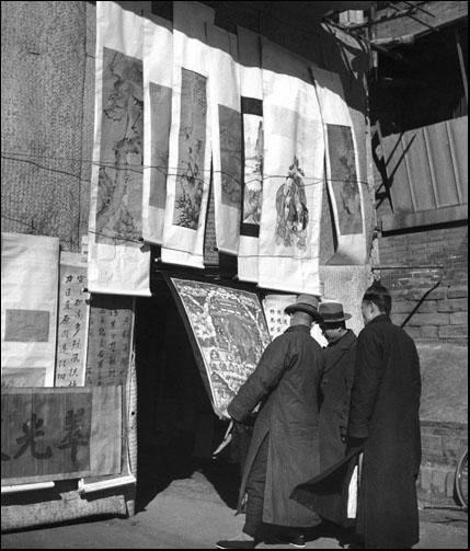ภาพเขียนมงคลต่างๆ ที่จำหน่ายในตลาดปีใหม่ ช่วงเทศกาลปีใหม่จีน โดยตลาดปีใหม่จีนนั้น เริ่มมีมาตั้งแต่ต้นยุคราชวงศ์ชิง (ค.ศ. 1664 - 1911) จัดเป็นตลาดที่มีแผงค้าขายมากมาย มากกว่า 1,000 ราย ก่อนหยุดชะงักไปในปีค.ศ. 1964 และกลับมาเปิดอีกครั้งในปี ค.ศ. 2001 (ภาพเฮดดา มอร์ริสัน)