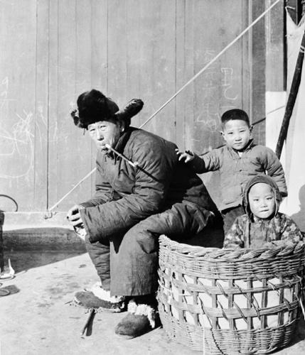 ภาพนี้สันนิษฐานว่า ชายสูงอายุและเด็กๆ ในภาพเป็นชาวบ้านรอบกรุงปักกิ่งที่เดินทางเข้ามาค้าขายในเมืองยุคนั้น ประตูไม้ด้านหลังยังเห็นลายมือเขียนด้วยชอล์ก คงจะเป็นของเด็กๆ (ภาพเฮดดา มอร์ริสัน)