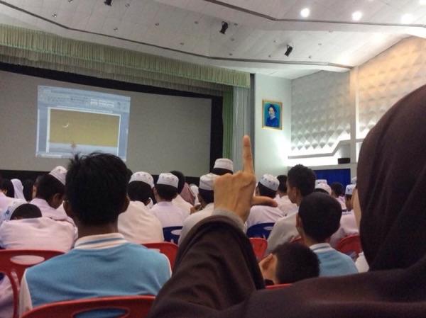 นักเรียนที่มาฟังการบรรยายทำมือเป็นรูปฉากเพื่อวัดมุมระหว่างดวงอาทิตย์และดวงจันทร์ เพื่อการสังเกตดวงจันทร์วันกำหนดรอมฎอน