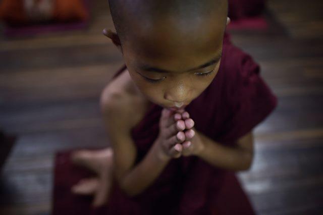 เณรรูปหนึ่งกำลังนั่งสวดมนต์ที่วัดแห่งหนึ่งซึ่งอยู่ในสังกัดองค์กร Mabatha (คณะกรรมการเพื่อการคุ้มครองชาติและศาสนา) แถบชานเมืองย่างกุ้งของพม่า (24 มิ.ย.)