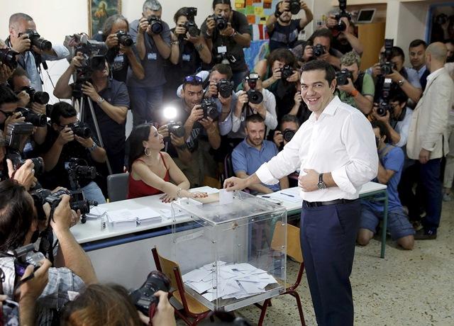 """<i><b>นายกรัฐมนตรี อเล็กซิส ซีปราส ของกรีซ ไปใช้สิทธิออกเสียงลงประชามติที่หน่วยลงคะแนนแห่งหนึ่งในกรุงเอเธนส์วันอาทิตย์ (5 ก.ค.) รัฐบาลที่นำโดยฝ่ายซ้ายจัดของเขา รณรงค์เรียกร้องให้ประชาชนออกเสียง """"ไม่ยอมรับ"""" มาตรฐานเข้มงวดทางเศรษฐกิจแลกกับการได้เงินช่วยเหลือจากเจ้าหนี้ระหว่างประเทศ ถึงแม้จะถูกบรรดาเจ้าหนี้เตือนว่า หากเสียง """"ไม่ยอมรับ"""" เป็นฝ่ายชนะในการลงประชามติคราวนี้ ก็อาจหมายถึงการที่กรีซจะต้องออกจากยูโรโซน</i></b>"""