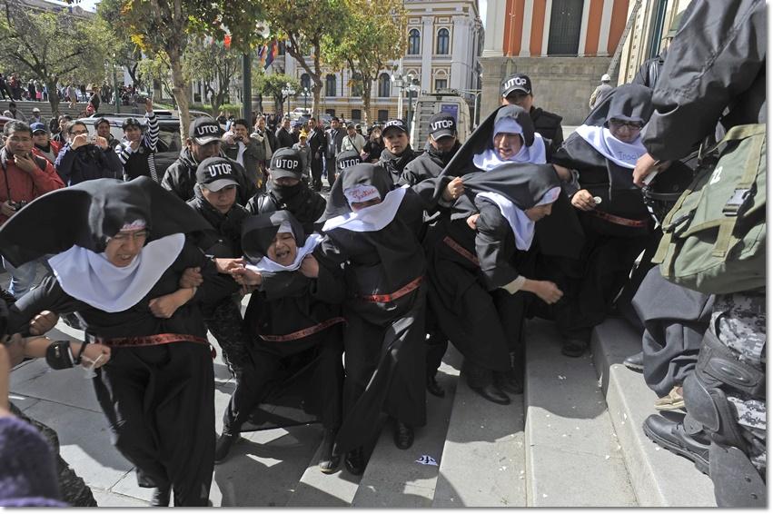 """สมาชิกของกลุ่มนักเคลื่อนไหวสตรี """"Mujeres Creando"""" หรือ ผู้หญิงสร้าง ต่างแต่งกลายเลียบแบบแม่ชี เพื่อประท้วงต่อการมาเยือนของสมเด็จพระสันตะปาปาฟรานซิสที่โบลิเวีย โดยคนทั้งหมดถูกตำรวจปราบจลาจลโบลิเวียจับกุมหน้าโบสถ์เมโทรโปลิแตน คาทริดรอล (Metropolitan Cathedral) ในกรุงลาปาซ ในวันที่ 6 กรกฎาคม (ภาพเอเอฟพี)"""