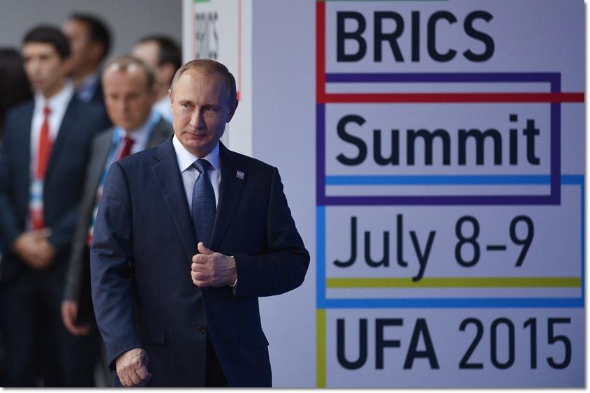 ประธานาธิบดีรัสเซีย วลาดิมีร์ ปูติน กำลังก้าวเข้าสู่ฮอลที่จัดแสดงผลงานศิลปะภาพครอบครัวที่การประชุม BRICS ซัมมิต ครั้งที่ 7 ที่เมือง UFA รัสเซีย ในวันที่ 9 กรกฎาคม(ภาพเอเอฟพี)