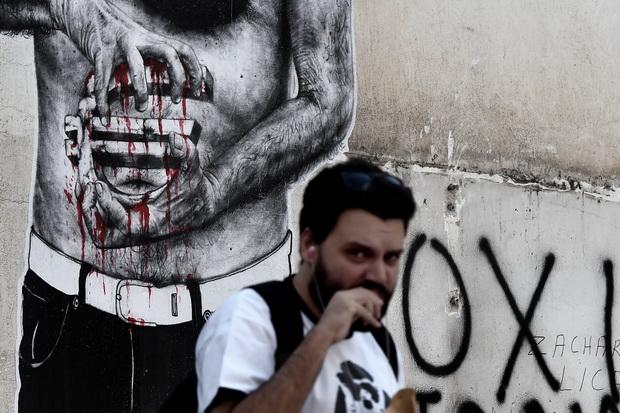 ชายคนหนึ่งเดินผ่านภาพวาดบนกำแพงเลือดกำลังไหลออกจากลัญลักษณ์ยูโร ใจกลางกรุงเอเธนส์ในวันอังคาร(14ก.ค.) โดยในวันเดียวกัน นายอเล็กซิส ซีปราส นายกรัฐมนตรีกรีซ นัดประชุมพรรคที่เขาต้องเผชิญภารกิจหนักในการในการกล่อมรัฐสภายอมรับมาตรการรัดเข็มขัดที่หนักหนาสาหัสกว่าเดิมให้ลุล่วงภายในวันพุธ (15 ก.ค.)