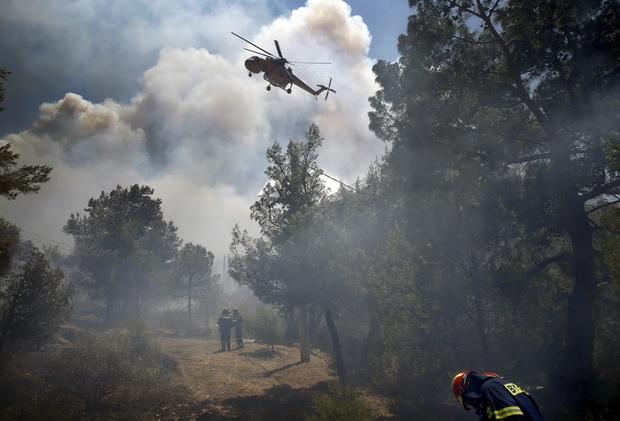 เฮลิคอปเตอร์นำน้ำลงไปทิ้งใส่กองเพลิงที่กำลังลุกโชน บริเวณชานกรุงเอเธนส์ของกรีซเมื่อวันศุกร์(17ก.ค.) หลังเกิดไฟป่า จนชาวบ้านต้องหลบหนีออกจากที่พักอาศัย