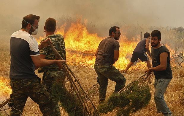 ทหารและชาวบ้านพยายามช่วยกันดับเพลิงที่กำลังโหมกระพือในเขตลาโกเนีย ภูมิภาคเพโลพอนนีส ทางตอนใต้ของกรีซ