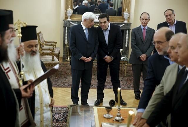 <b><i>นายกรัฐมนตรี อเล็กซิส ซีปราส ของกรีซ (ด้านหลัง ที่3จากขวา) และประธานาธิบดีโปรโคปิส ปัฟโลปูโลส (ด้านหลัง ที่4จากขวา) สนทนากันในระหว่างพิธีสาบานตนทางศาสนา ของผู้ที่ได้รับแต่งตั้งเป็นรัฐมนตรีใหม่  ณ ทำเนียบประธานาธิบดีในกรุงเอเธนส์เมื่อวันเสาร์ (18 ก.ค.) </b></i>