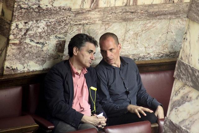 <b><i>อดีตรัฐมนตรีคลัง ยานิส วารูฟากิส ของกรีซ (ขวา) สนทนากับ ยูคลิด ซากาโลโตส รัฐมนตรีคลังคนปัจจุบัน ระหว่างการประชุมของรัฐสภาในกรุงเอเธนส์เมื่อวันที่ 9 ก.ค.  ในการให้สัมภาษณ์บีบีซีซึ่งนำออกมาเผยแพร่วันเสาร์ (18) วารูฟากิส วิจารณ์ว่าเงื่อนไขใหม่ๆ อันเข้มงวดจากฝ่ายเจ้าหนี้ จะกลายเป็นความหายนะของการบริหารเศรษฐกิจมหภาคครั้งร้ายแรงที่สุดในประวัติศาสตร์ </b></i>