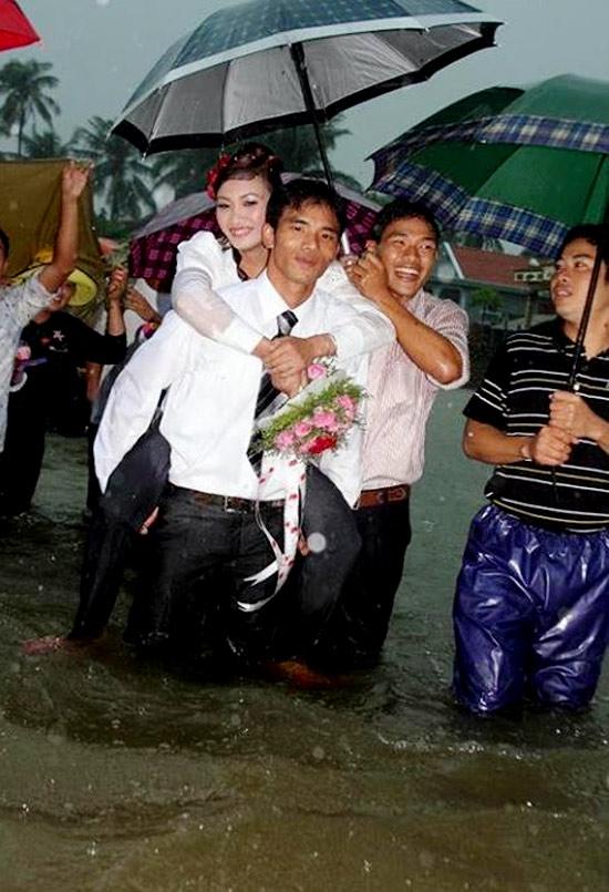 <FONT color=#00003>เจ้าสาวและเจ้าบ่าว ดูสีหน้าเปี่ยมสุข .. เพื่อนเจ้าบ่าวกับญาติอีกคนกางร่มกันฝน เดินลุยน้ำสูงเหนือเข่าไปด้วยกัน ทุกคนสรวลเสเฮฮา ญาติๆ ที่เกาะกลุ่มกันเดินตาม ต่างยิ้มระรื่น. </b>