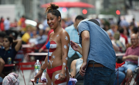 New York, New York, UNITED STATES: A young woman has her body painted in preparation for posing for photos with tourists in Times Square August 19, 2015 in New York. Mayor Bill de Blasio said that he sees the desnudas in Times Square as pushy panhandlers whose efforts to separate tourists from their money should be regulated. AFP PHOTO/Don Emmert