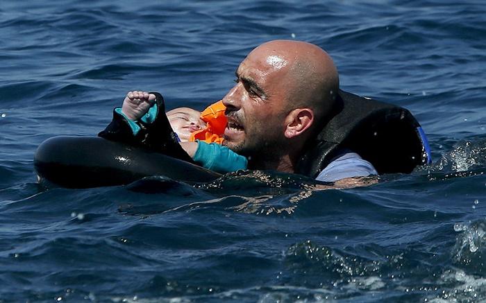 ผู้อพยพชาวซีเรียรายหนึ่งถูกบันทึกภาพขณะพยายามว่ายน้ำไปขึ้นบกที่เกาะเลสบอสของกรีซ    โดยมีลูกน้อยของเขานอนหลับด้วยความอ่อนเพลียอยู่ในห่วงยางชูชีพ