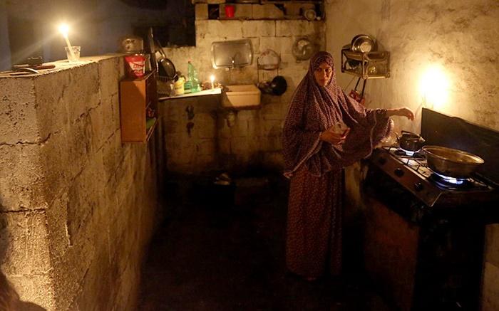 สตรีชาวปาเลสไตน์ถูกบันทึกภาพขณะทำครัวภายใต้แสงเทียนภายในบ้านหลังหนึ่งที่เมืองเบท ลาเฮีย   ทางตอนเหนือของฉนวนกาซาที่เป็นบ้านของประชากรราว 1.8 ล้านคน  ซึ่งต้องทนทุกข์กับปัญหาขาดแคลนกระแสไฟฟ้านานหลายชั่วโมงต่อวัน