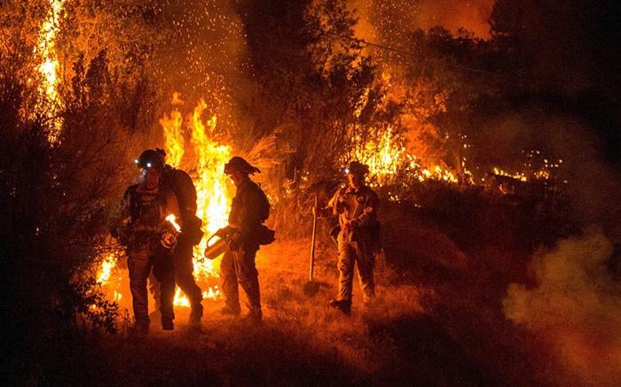 เจ้าหน้าที่ดับเพลิงกลุ่มหนึ่งถูกบันทึกภาพขณะพยายามควบคุมการลุกลามของไฟป่าใกล้กับเมืองซาน แอนเดรส  ในมลรัฐแคลิฟอร์เนียของสหรัฐฯ