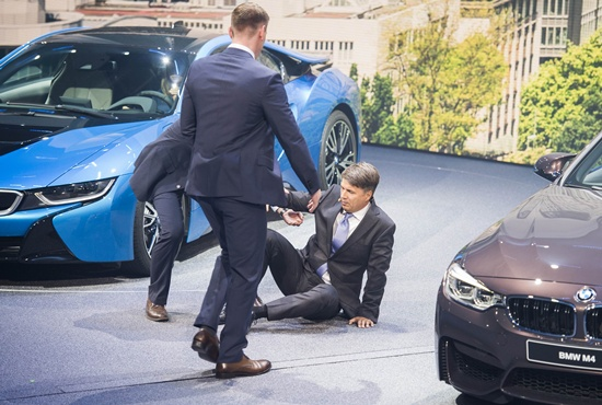 Frankfurt am Main, Hessen, GERMANY: CEO of BMW Harald Krueger is assisted after falling to the ground during a presentation at the 66th IAA auto show in Frankfurt on September 15, 2015. Hundreds of thousands of visitors are expected to crowd into the massive exhibition halls of Frankfurts sprawling trade fair grounds later this week to catch a glimpse of the latest models and high tech innovations. AFP PHOTO/Odd Andersen