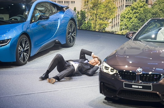 Frankfurt am Main, Hessen, GERMANY: CEO of BMW Harald Krueger falls to the ground during a presentation at the 66th IAA auto show in Frankfurt on September 15, 2015. Hundreds of thousands of visitors are expected to crowd into the massive exhibition halls of Frankfurts sprawling trade fair grounds later this week to catch a glimpse of the latest models and high tech innovations. AFP PHOTO/Odd Andersen
