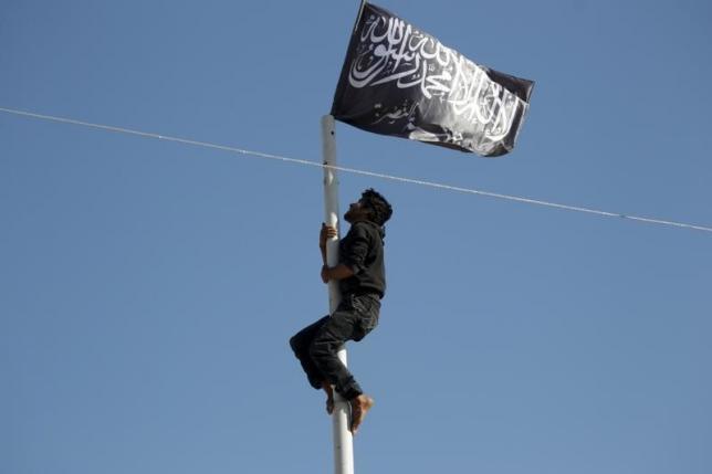สมาชิกกลุ่มติดอาวุธ อัล-นุสรา ฟรอนท์ ปีนขึ้นไปบนเสาเพื่อติดธงสัญลักษณ์ของกลุ่มเหนือจตุรัสใจกลางเมืองอารีฮา จ.อิดลิบ หลังเข้ายึดเมืองดังกล่าวไว้ได้เมื่อเดือนพฤษภาคม (แฟ้มภาพ)