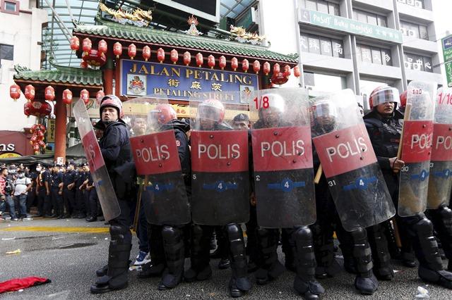 """ภาพจากแฟ้มถ่ายเมื่อวันที่ 16 กันยายน 2015 ขณะตำรวจปราบจลาจลของมาเลเซียตั้งแถวคอยปกป้องกลุ่มผู้ชุมนุมเดินขบวน """"เสื้อแดง"""" ที่เป็นพวกโปรนายกรัฐมนตรีนาจิบ ราซัค และโปรพรรคอัมโน แกนนำรัฐบาลผสม ซึ่งมีบางส่วนทำท่าจะบุกเข้าไปในเขต """"ไชน่าทาวน์"""" หรือ ตลาดถนนเปตาลิ่ง ในกรุงกัวลาลัมเปอร์"""
