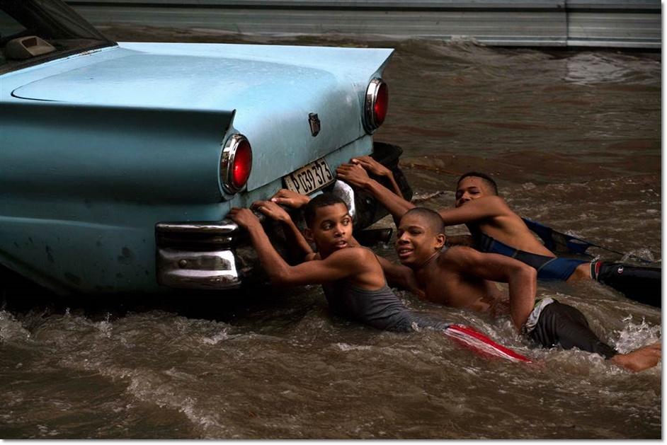 เด็กชายชาวคิวบา 3 คนเกาะท้ายรถยนต์อเมริกันรุ่นคลาสสิคในระหว่างเกิดน้ำท่วมฉับพลันหลังฝนตกหนักในกรุงฮาวานา คิวบาวันที่ 14 ตุลาคม