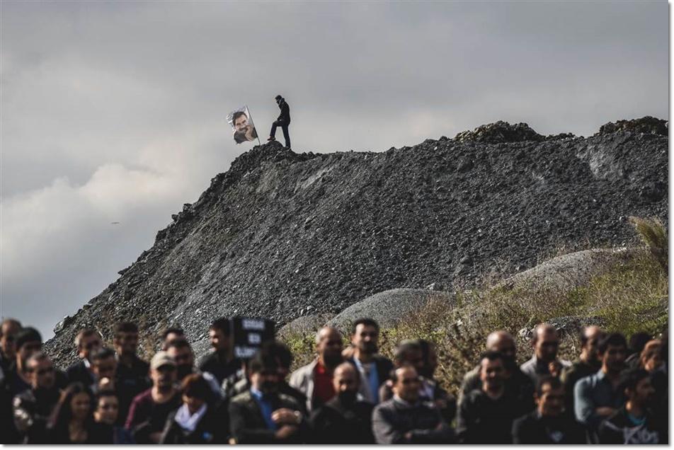 ผู้คนร่วมงานศพของเซอร์ดาร์ เบน (Serdar Ben) หนึ่งในเหยื่อระเบิดแรลลีหยุดความรุนแรงในกรุงอังการา ในขณะที่มีชายที่ร่วมงานได้ปักธงรูป อับดุลเลาะฮ์ โอคาลาน ( Abdullah Ocalan) ผู้นำพรรคแรงงานเคิร์ดที่อยู่ในระหว่างการจำคุก บริเวณเนินเขาในเมืองอิสตันบุลวันที่ 15 ตุลาคม
