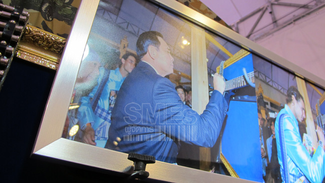 """นายกฯ เซ็นชื่อลงบนตัวกีตาร์ ระหว่างเที่ยวชมงาน  """"สุดยอด SMEs ของดีทั่วไทย"""" ที่คลองผดุง กรุงเกษม ข้างทำเนียบรัฐบาล"""