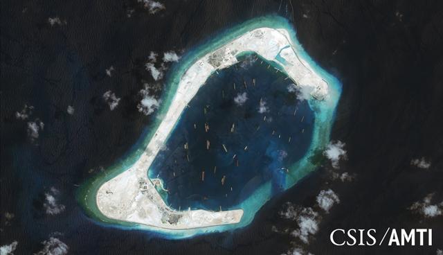 """<i> เกาะปะการัง """"ซูบิ"""" ซึ่งตั้งอยู่ในหมู่เกาะสแปรตลีย์ ของทะเลจีนใต้  ที่จีนถมทะเลและทำการก่อสร้างสิ่งต่างๆ จำนวนมาก ในภาพถ่ายดาวเทียมซึ่งเผยแพร่โดยศูนย์เพื่อการศึกษายุทธศาสตร์และการระหว่างประเทศ (CSIS) ในสหรัฐฯ  ภาพนี้ถ่ายไว้เมื่อวันที่ 3 กันยายน 2015  ทางการสหรัฐฯแถลงว่าได้ส่งเรือรบ ยูเอสเอส แลสเสน แล่นเฉียดเกาะเทียมแห่งนี้ในวันอังคาร (27ต.ค.) ที่แล้ว </i>"""