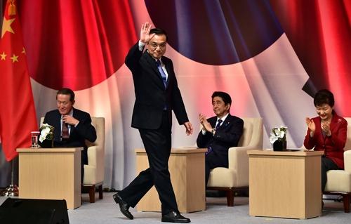 นายกรัฐมนตรี หลี่ เค่อเฉียง ของจีน (ยืน) , นายกรัฐมนตรี ชินโซ อาเบะ ของญี่ปุ่น (นั่งกลาง) , ประธานาธิบดี พัค กึน-ฮเย ของเกาหลีใต้ (นั่งขวา) ได้ร่วมประชุมไตรภาคีที่กรุงโซล ประเทศเกาหลีใต้