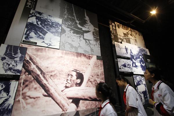 เด็กนักเรียนกำลังดูภาพในหอรำลึกการสังหารหมู่ที่นานกิง ภาพเมื่อวันที่ 10 ต.ค. 2558 (ภาพ เอเอฟพี)