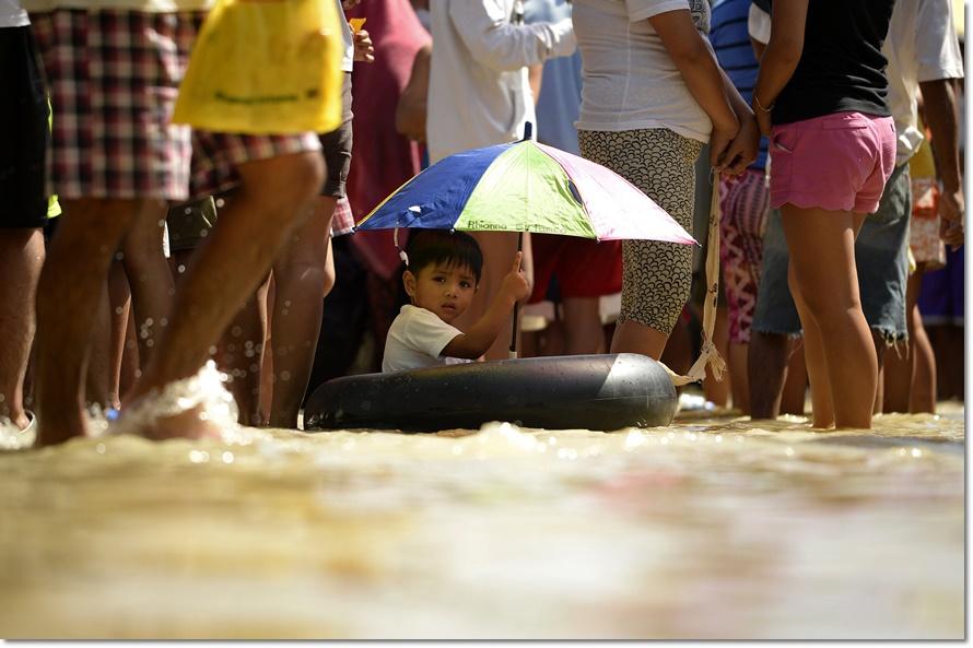 หลังพายุไต้ฝุ่นเมลอร์ (Melor) เข้าเซ็นทรัลวิซายาส (the Central Visayas) ในวันที่ 14 ธันวาคมที่ผ่านมา  เด็กหญิงชาวฟิลิปปินส์คนหนึ่งนั่งบนยางรถยนต์กางร่มในน้ำท่วมเมื่อวันพฤหัสบดี (24 ธ.ค) ท่ามกลางประชาชนในพื้นที่เข้าคิวรอรับของบริจาคช่วยผู้ประสบภัยที่ คาลัมปิต บูลาคาน (Calumpit Bulacan) ทางเหนือกรุงมะนิลา