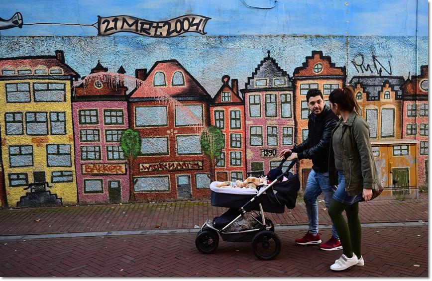 อาห์หมาด (Ahmad) และอาเลีย( Alia)  ผู้ลี้ภัยที่รอดชีวิตจากระเบิดโจมตีในกรุงแบกแดด อิรัก ในปี  2014 กำลังเดินพร้อมทารกผ่านภาพวาดบนกำแพงใน ลีวาร์เดน (Leeuwarden) เนเธอร์แลนด์