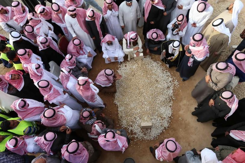 """สมาชิกราชวงศ์ซาอุดีอาระเบียยืนไว้อาลัยรอบหลุมฝังศพ หรือ """"กุโบร์"""" ของสมเด็จพระราชาธิบดีอับดุลเลาะห์ ที่สุสานอัล-อูด ในกรุงริยาด เมื่อวันที่ 23 ม.ค. 2015"""