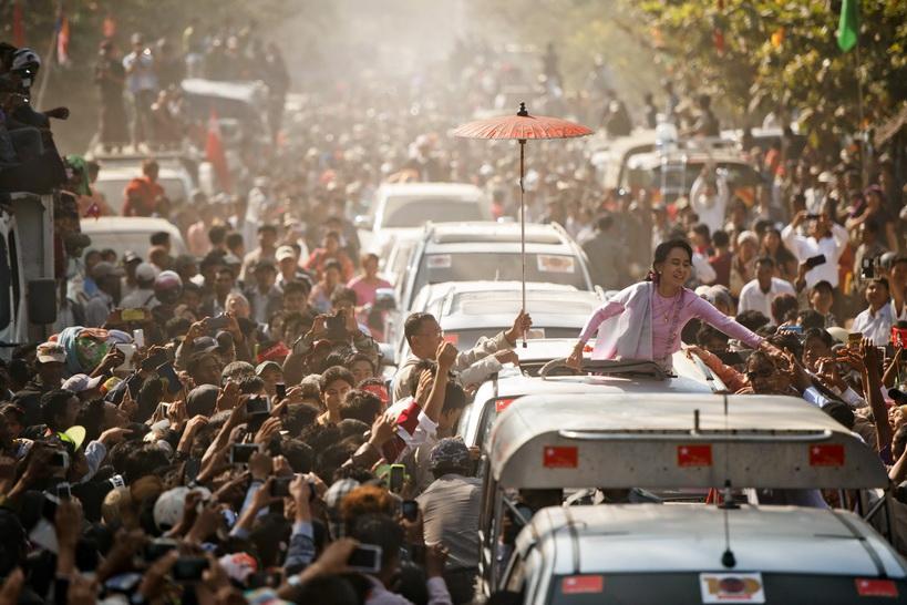 อองซานซูจี วีรสตรีนักต่อสู้เพื่อประชาธิปไตยแห่งพม่า โบกมือทักทายผู้สนับสนุนหลังเดินทางออกจากสถานที่จัดพิธีรำลึก 100 ปีวันเกิดนายพลอองซาน ที่เมืองนัตหมอก (Natmauk) ทางตอนกลางของพม่า เมื่อวันที่ 13 ก.พ. หลังจากยืนหยัดต่อสู้ระบอบเผด็จการทหารมานานร่วม 30 ปี ในที่สุดซูจีก็ได้ก้าวมาถึงขอบประตูสู่อำนาจสูงสุดทางการเมือง เมื่อพรรคสันนิบาตแห่งชาติเพื่อประชาธิปไตย (เอ็นแอลดี) ของเธอสามารถคว้าชัยชนะอย่างถล่มทลายในการเลือกตั้งทั่วไปของพม่าเมื่อเดือน พ.ย.